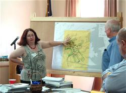 A woman talking while pointing at a map