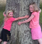 Two young girls hugging a tree